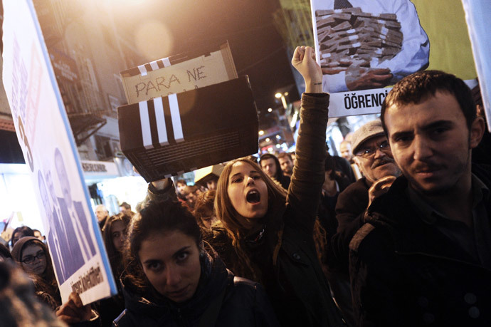 Protestors chant slogans and hold up shoe boxes as they march to the entrance of a Halkbank bank branch in the Besiktas district of Istanbul on December 19, 2013.( AFP Photo / Ozan Kose)