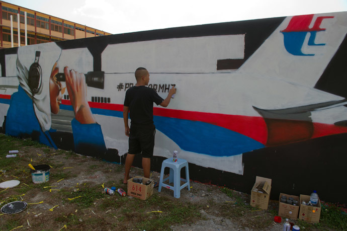 A member from Super Sunday, Zulkifli Salleh works on a graffiti featuring the missing Malaysia Airlines flight MH370 displayed on a wall in Kuala Lumpur on March 24, 2014. (AFP Photo)