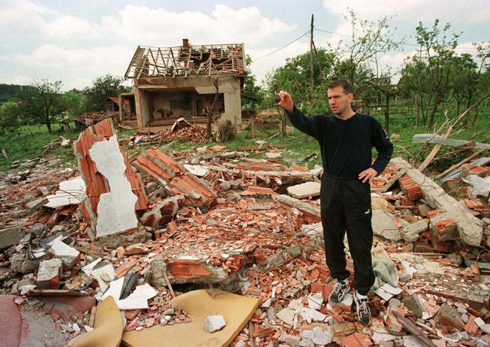 Vladan Lukic, a leading Yugoslav soccer player, shows a destroyed house, where Stevan (8) and Dajana Pavlovic (7) were killed during recent NATO bombing in Ralja near Belgrade June 26, 1999 (Reuters)