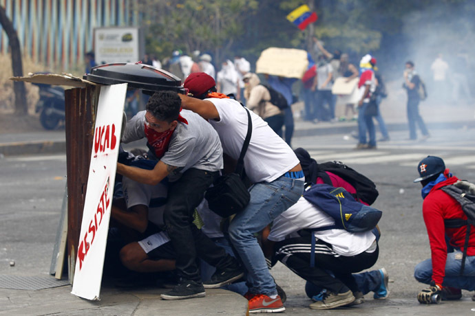 Anti-government protesters take cover behind makeshift shields during clashes with riot police in Caracas March 20, 2014. (Reuters)