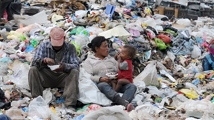 A couple and their child have breakfast amid the garbage at the municipal rubbish dump, 20 km north of Tegucigalpa, Honduras. (AFP Photo / Orlando Sierra)