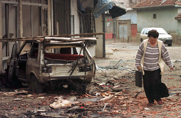 A woman passes a destroyed car March 28,1999 after a NATO missile hit downtown of Kosovo's capital of Pristina in Saturday night's NATO attack (Reuters)
