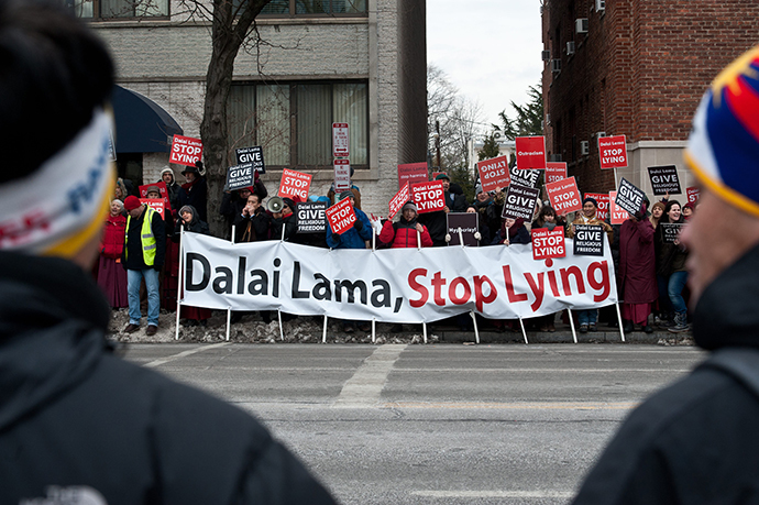 "Supporters of Tibetan spiritual leader the Dalai Lama (front) watch members of the International Shugden Community protesting the Dalai Lama's ""forcibly banning the religious practice of the Buddha Dorje Shugden and openly discriminating against people of this religious faith"" outside the National Cathedral in Washington,DC on March 7, 2014. (AFP Photo / Nickolas Kamm)"