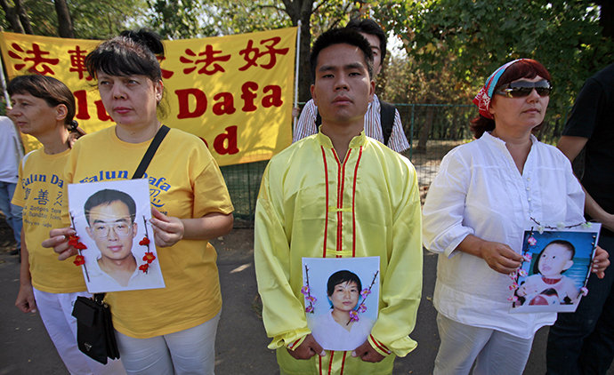 Falun Gong practitioners hold portraits of fellow Chinese practitioners as they protest against China's crackdown on Falun Gong followers in front of the Chinese embassy in Bucharest September 24, 2011. (Reuters / Radu Sigheti)