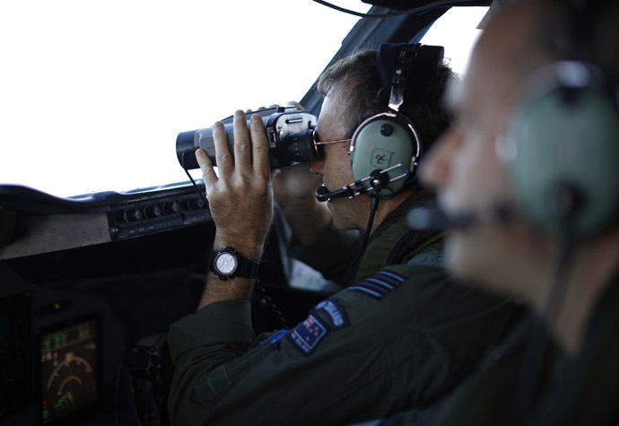 Wing Commander Rob Shearer looks through binoculars on the flight deck of a Royal New Zealand Air Force P-3K2 Orion aircraft during a search for the missing Malaysian Airlines flight MH370 over the southern Indian Ocean, March 29, 2014. (Reuters)