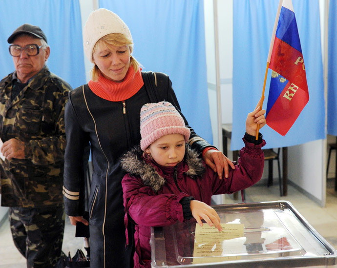 A child casts her mother's ballot while holding a Russian flag at a polling station on March 16, 2014 in Simferopol. (AFP Photo / Viktor Drachev)