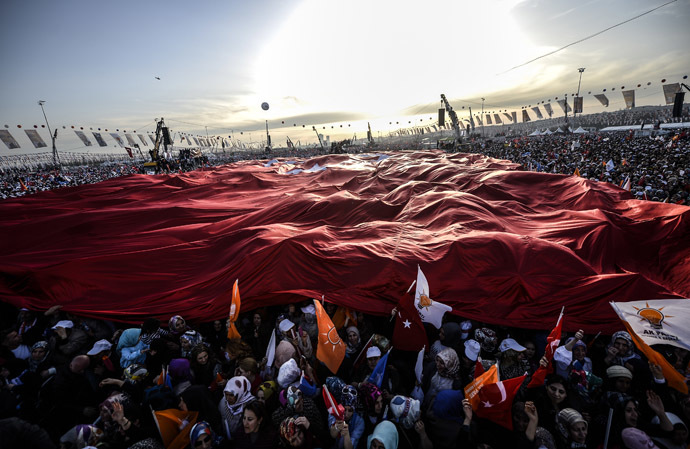 Supporters of Turkey's Prime Minister cheer and wave Turkish and AK Party (AKP) flags during an election rally in Istanbul on March 23, 2014. (AFP Photo)