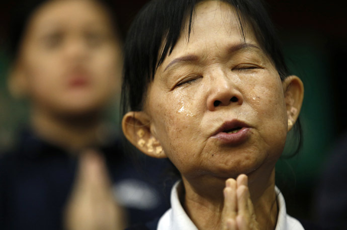 A Taiwanese volunteer assisting relatives of passengers on board Malaysia Airlines MH370 cries as she prays for the passengers at the Lido Hotel in Beijing April 1, 2014. (Reuters)