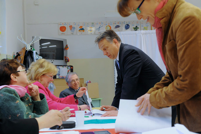 Hungarian Prime Minister Viktor Orban (C) chats with an election officals as his wife Aniko Levai (R) holds ballot papers in a polling station of a local school at12th district of Budapest on April 6, 2014.(AFP Photo / Attila Kisbenedek)
