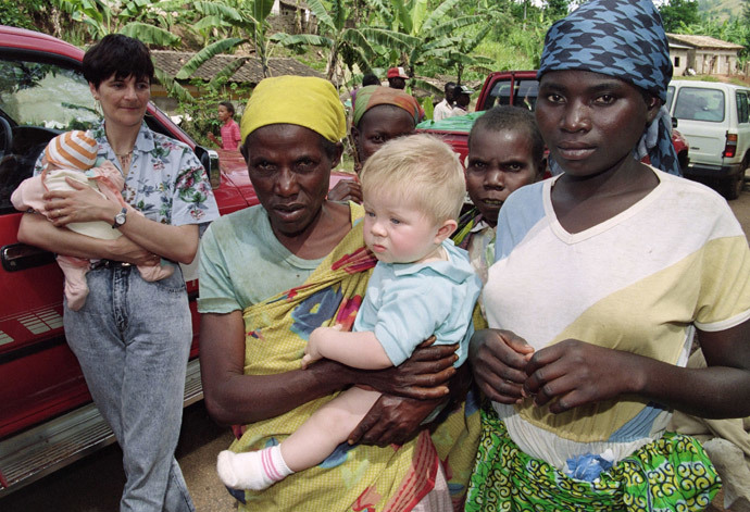A Rwandan woman carries a Swiss family's baby 09 April 1994 at Butare on the Rwanda-Burundi border where numerous foreigners were fleeing the civil clashes in Rwanda. (AFP Photo / Pascal Guyot)