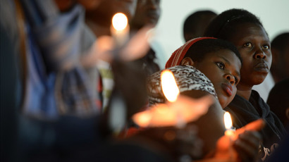 Rwandan women hold candles during a night vigil and prayer for genocide victims at the Amahoro stadium in Kigali, Rwanda, on April 7, 2014. (AFP Photo / Simon Maina)