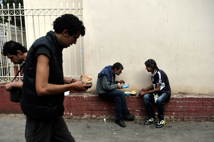 People eat after they received food donated by the Greek church in central Athens (AFP Photo)