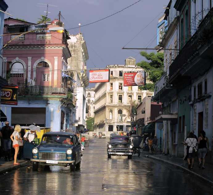 People walk as cars are driven on a street in Havana (Reuters)