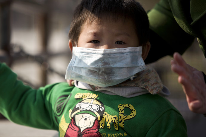 A boy wearing a mask is seen on a street during a hazy day in downtown Shanghai December 3, 2013. (Reuters)