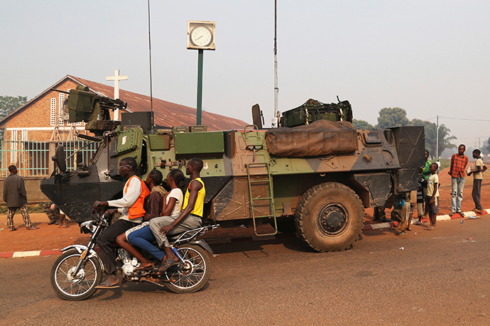 People ride on a motorcycle as they pass past a military vehicle in Wouango district January 9, 2014 (Reuters / Emmanuel Braun)