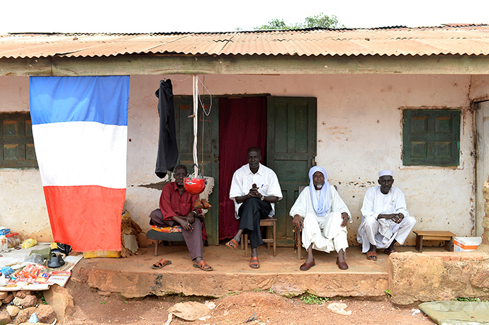 People sit next to a French flag in the village of Boda on April 7, 2014 (AFP Photo / Miguel Medina)