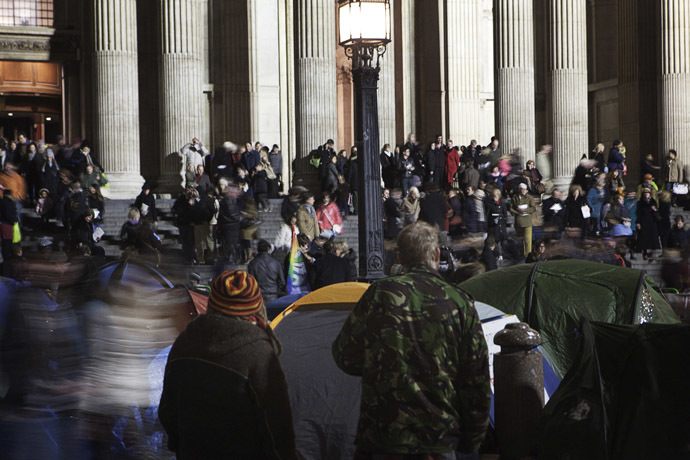 Occupy London Stock Exchange protestors watch as people leave a Christmas eve carol service at St Pauls Cathedral in London December 24, 2011. (Reuters)