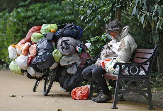 A homeless man sleeps on a park bench next to a bicycle with bags of his belongings in London (Reuters//Luke MacGregor)