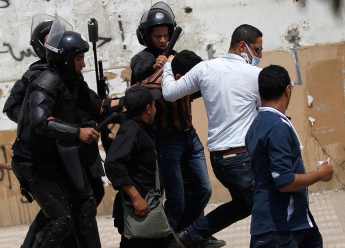 Riot police and a plainclothes policeman detains a student, who is a supporter of Muslim Brotherhood and ousted President Mohamed Mursi, during a protest against the military and the interior ministry, at Al-Azhar University in Cairo's Nasr City district, April 16, 2014. (Reuters / Amr Abdallah Dalsh)