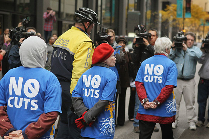 Demonstrators are led away by police during a protest against cuts to federal safety net programs, including Social Security, Medicare, and Medicaid on November 7, 2011 in Chicago, Illinois. (AFP Photo / Getty Images / Scott Olson)