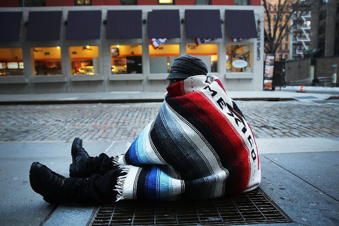 Prince, who is homeless, sits on a subway grate to keep warm on a frigid day on January 7, 2014 in New York, United States. (AFP Photo / Getty Images / Spencer Platt)