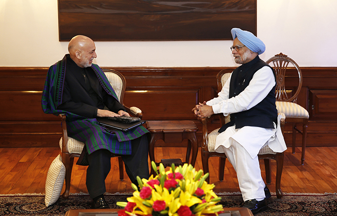 Indian Prime Minister Manmohan Singh (R) talks to Afghan President Hamid Karzai at his residence in New Delhi on December 13, 2013. (AFP Photo / Saurabh Das)