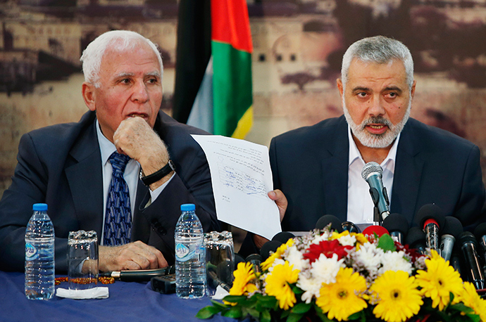Head of the Hamas government Ismail Haniyeh shows a signed reconciliation agreement as he attends a news conference with Senior Fatah official Azzam Al-Ahmed (L) in Gaza City April 23, 2014 (Reuters / Suhaib Salem)