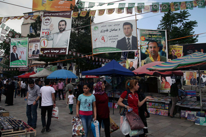 People walk past campaign posters for Iraq's parliamentary elections in Sulaimaniya April 28, 2014. Picture taken April 28, 2014. (Reuters / Yahya Ahmad)