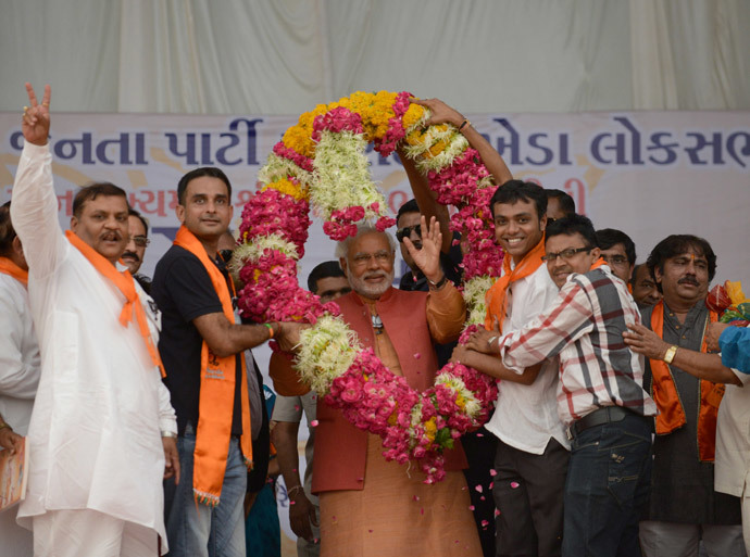 Chief Minister of the western Indian state of Gujarat and Bharatiya Janata Party (BJP) Prime Ministeral candidate Narendra Modi (C) gestures as he is offered a garland of flowers by supporters during an election rally in Vallabh Vidyanagar, some 85 kms from Ahmedabad on April 28, 2014. (AFP Photo / Sam Panthaky)