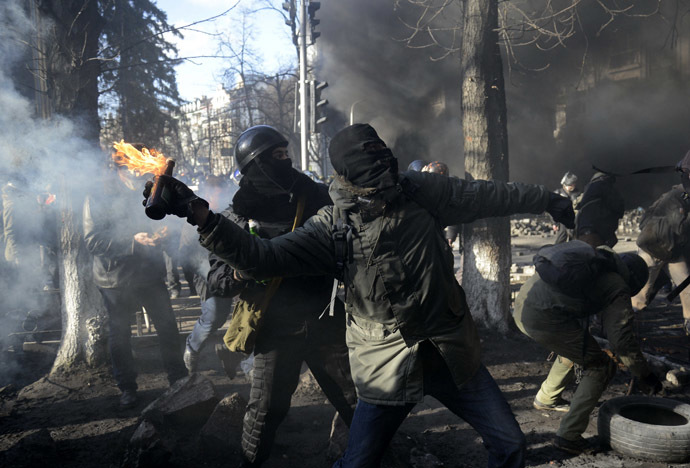 An anti-government protester throws a Molotov cocktail towards Interior Ministry members during clashes in Kiev, February 18, 2014. (Reuters/Maks Levin)