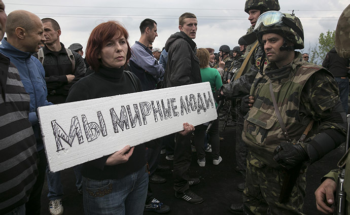 "A civilian holds a sign in front of Ukrainian troops at a checkpoint near the town of Slaviansk in eastern Ukraine May 2, 2014. The sign reads, ""We are peaceful people."" (Reuters / Baz Ratner)"