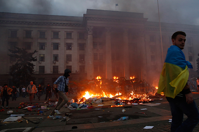 A protester wrapped in a Ukrainian flag walks past a burning tent camp and a fire in the trade union building in Odessa May 2, 2014 (Reuters / Yevgeny Volokin)