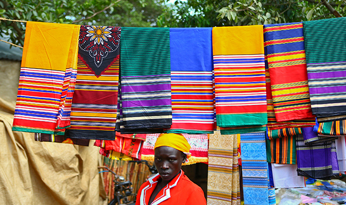 A trader from Bunia in eastern Democratic Republic of Congo sells fabric at a market at the Kyangwali refugee settlement in Hoima district in Western Uganda (Reuters / Edward Echwalu)