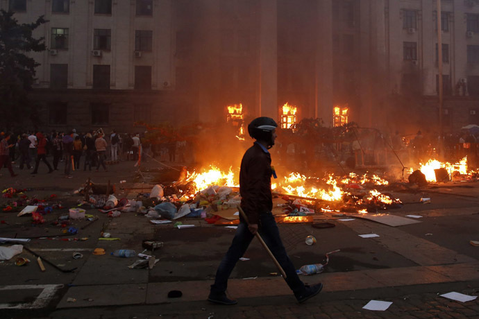 A protester walks past a burning tent camp and a fire in the trade union building in Odessa May 2, 2014. (Reuters/Yevgeny Volokin)