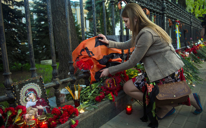A woman lays flowers by the fence of the Ukrainian embassy in Moscow on May 3, 2014, in honor of people killed during clashes in Odessa. (AFP Photo)