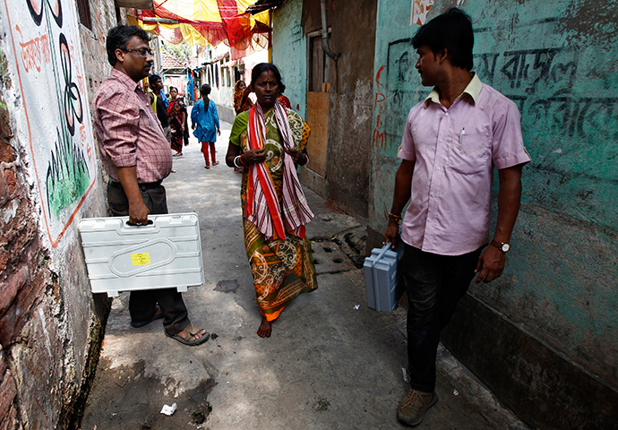 Polling officials carry electronic voting machines in an alley to demonstrate to residents how to use the machines during an awareness program at a red-light area in Kolkata May 6, 2014 (Reuters)