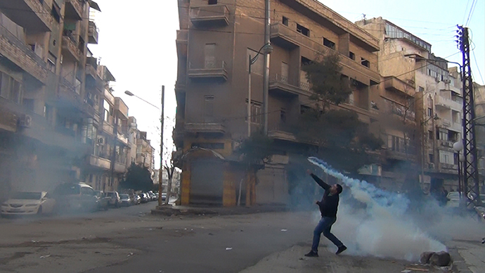 A protester in the flahspoint central Syrian city of Homs throws a tear gas bomb back towards security forces, on December 27, 2011. (AFP photo)