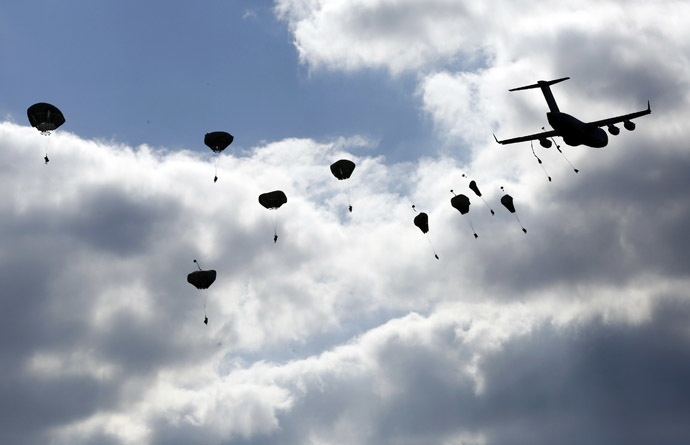 "Troops from the U.S. Army's 173rd Infantry Brigade Combat Team parachute from a Boeing C-17 Globemaster III during a NATO-led exercise ""Orzel Alert"" held together with Canada's 3rd Battalion and Princess Patricia's Light Infantry, and Poland's 6th Airborne Brigade in Bledowska Desert in Chechlo, near Olkusz, south Poland May 5, 2014. (Reuters/Kacper Pempel)"