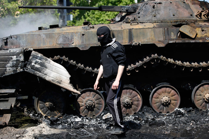 A masked man walks past a burnt-out armoured personal carrier near the city hall in Mariupol, eastern Ukraine May 10, 2014.(Reuters / Marko Djurica )