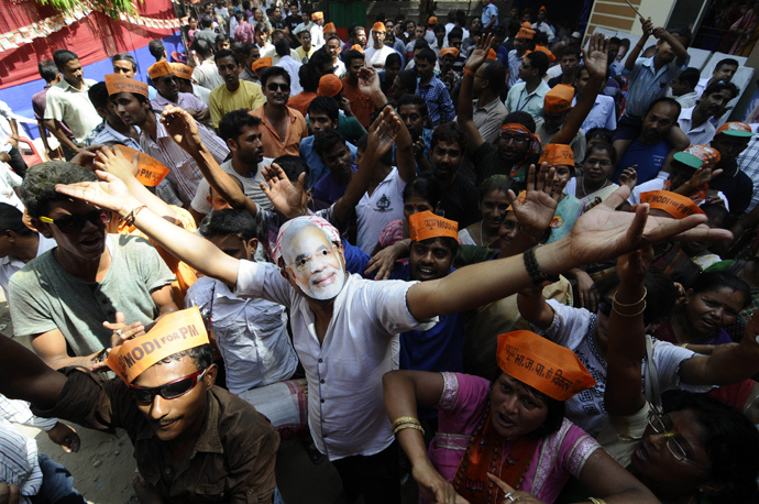 A Bharatiya Janata party (BJP) worker wears a mask of BJP prime ministerial candidate Narendra Modi as they celebrate outside the party office in Guwahati on May 16, 2014 (AFP Photo / Biju Boro)