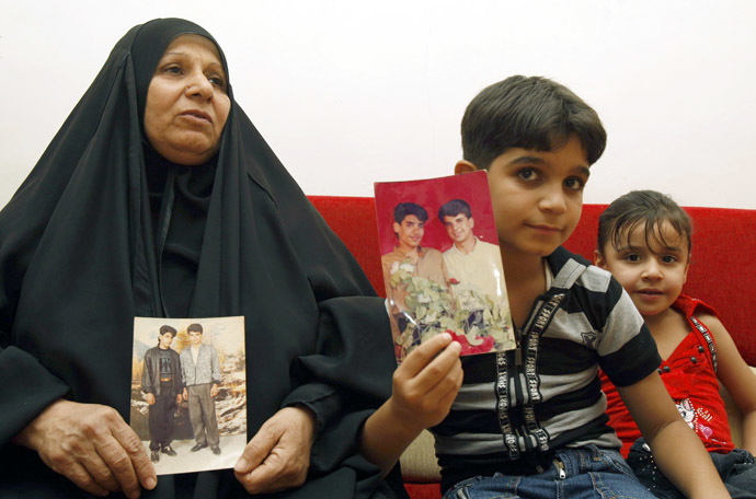 The mother and son of Baha Mousa (R in the picture), an Iraqi hotel receptionist who was kicked and beaten to death whilst in British Army custody, hold pictures of him at their house in Basra, 420 km (260 miles) southeast of Baghdad September 7, 2011.(Reuters/Atef Hassan)