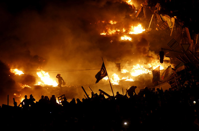 Anti-government protesters stand behind burning barricades in Kiev's Independence Square February 19, 2014. (Reuters/Vasily Fedosenko)