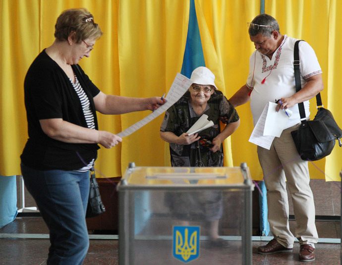 A man assists a woman with the casting of her ballot at polling station in the southern Ukrainian city of Dnipropetrovsk on May 25, 2014. (AFP Photo / Anatolii Stepanov)