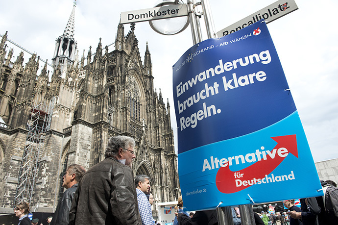 "A placard reading ""Immigration needs to be regulated in a clear way"" hangs on a lamp post during an election rally of Germany's anti-Euro Alternative Fuer Deutschland (AFD - Alternative for Germany) Party, before the European Parlament elections, in front of Cologne's cathedral on April 26, 2014 (AFP Photo / John Macdougall)"