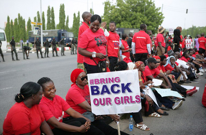 Members of civil society groups and organizations carry placards as the take part in a protest against the abduction of the Chibok schoolgirls, after they were prevented from reaching the president's residence in Abuja on May 22, 2014. (AFP Photo / Wole Emmanuel)