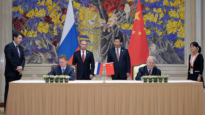 China's President Xi Jinping (back R) and Russia's President Vladimir Putin (back L) attend an agreement signing ceremony in Shanghai on May 21, 2014, with Gazprom CEO Alexei Miller (front L) and Chinese state energy giant CNPC Chairman Zhou Jiping (front R) signing an agreement. (AFP Photo / Alexey Druzhinin)
