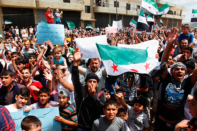 Syrian refugees carrying Free Syrian Army flags attend a protest against the election of Syrian President Bashar Al-Assad in Tripoli June 1, 2014 (Reuters / Omar Ibrahim)
