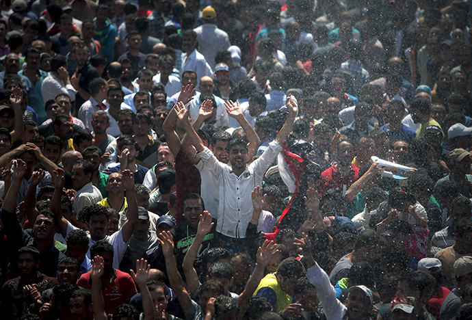 Men celebrate, before voting for the upcoming presidential elections in Syria, outside the Syrian Embassy in Yarze east of Beirut on May 28, 2014 (AFP Photo)