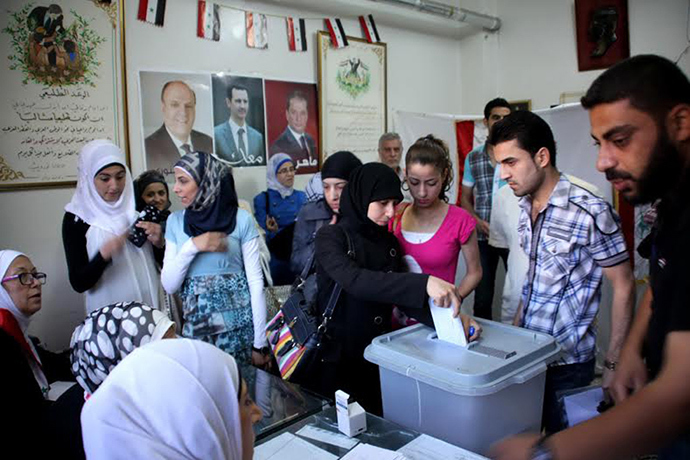 A handout picture released by the official Syrian Arab News Agency (SANA) on June 3, 2014 shows citizens voting in presidential election at a polling station in a regime-held area in Aleppo (AFP Photo / SANA)