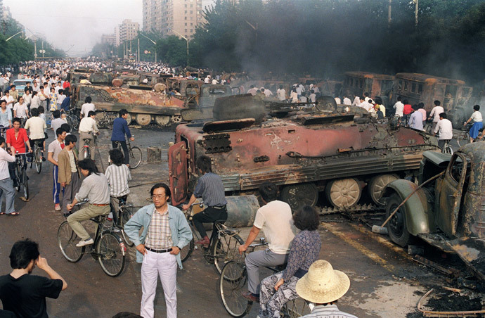 (FILES) In a ilfe picture taken on June 4, 1989 Beijing residents gather around the smoking remains of over 20 armoured personnel carriers burnt by demonstrators during clashes with soldiers near Tiananmen Square. (AFP Photo / Files / Manuel Ceneta)